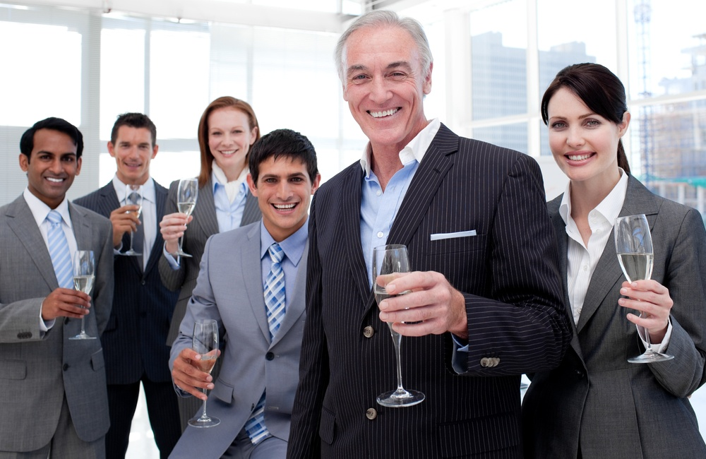 Smiling inernational business team holding glasses of Chamoagne to celebrate a success.jpeg