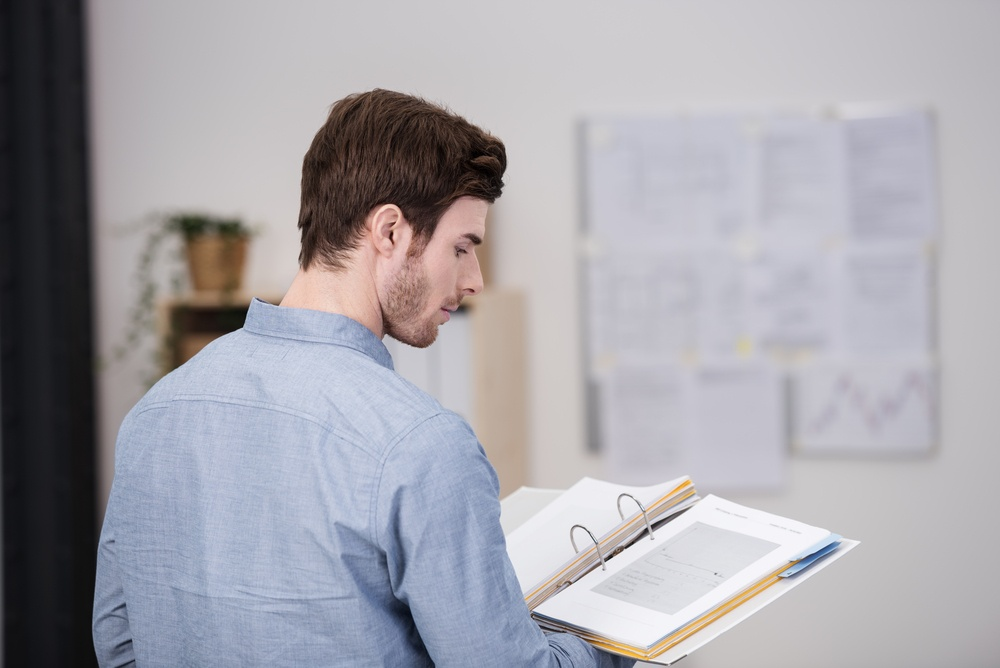 Young man standing doing research in the office reading from a hardcover book balanced on his palm, view over his shoulder from the rear.jpeg